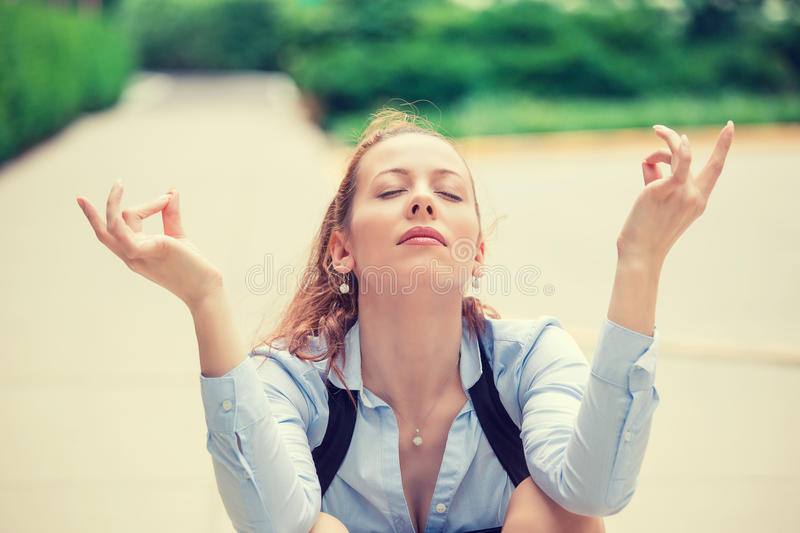 Business woman eyes closed hands raised in air relaxing meditating royalty free stock image