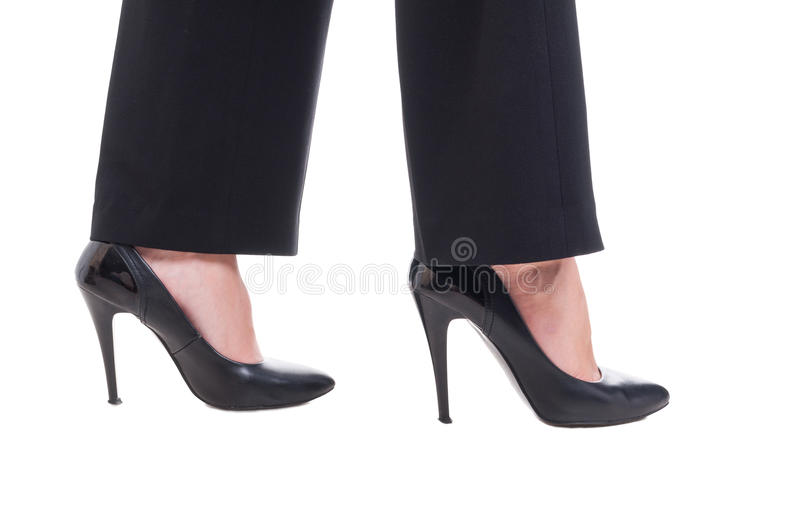 Business woman feet wearing black leather shoes with high heels. Isolated on white studio background royalty free stock photo