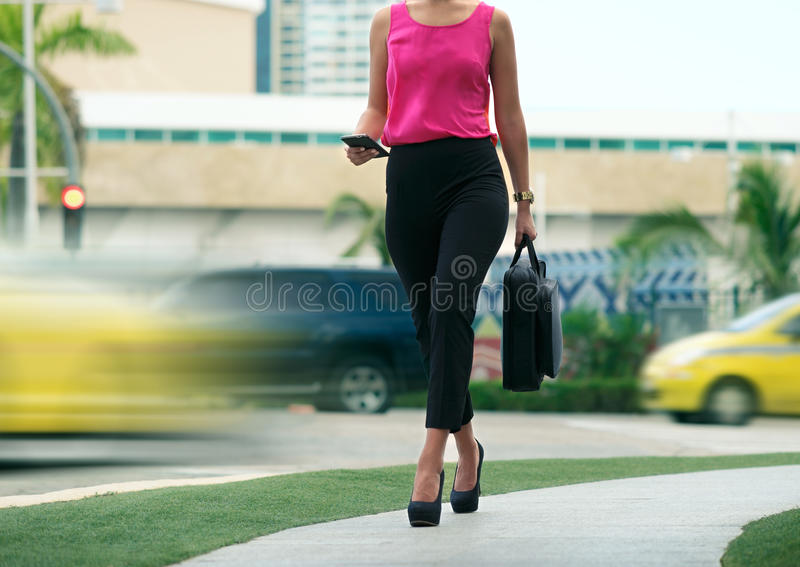 Business woman female commuter going to office by walk. Cropped view of business woman walking in city street with laptop bag, chatting on mobile phone and going royalty free stock photography