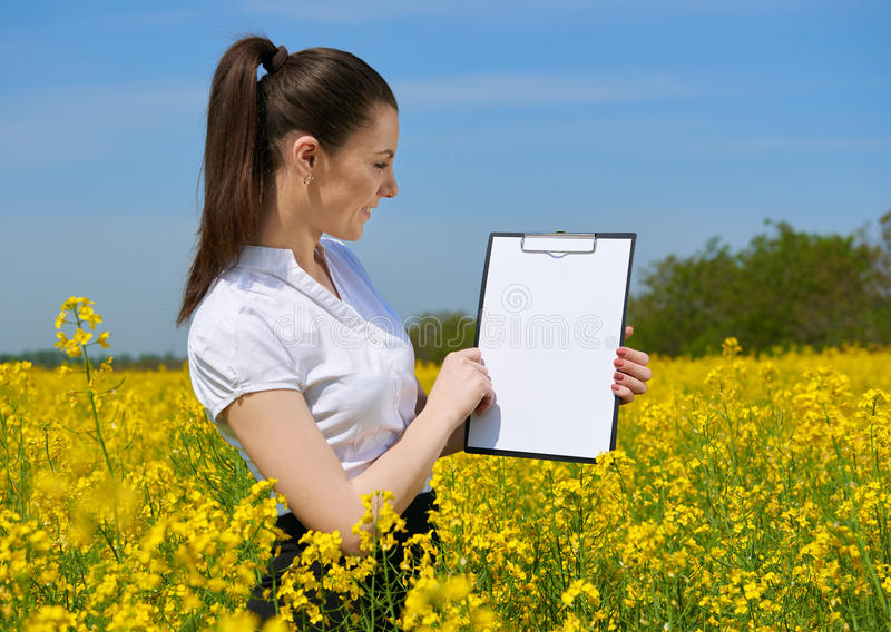Business woman in flower field outdoor look on clipboard. Young girl in yellow rapeseed field. Beautiful spring landscape, bright. Sunny day stock photo
