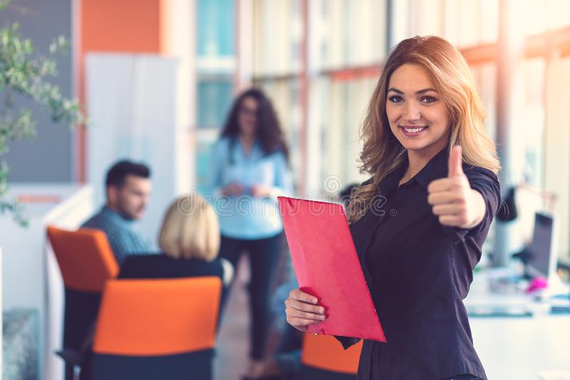 Business woman with folders standing and team mates working in meeting room at office. royalty free stock photography