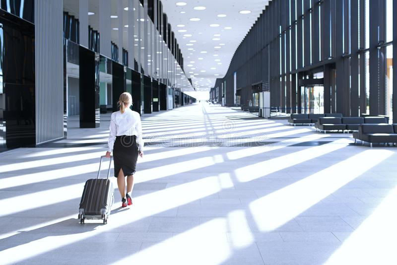 Business woman walking with wheeled bag. Business woman in formal clothing walking with wheeled bag at airport terminal royalty free stock photos