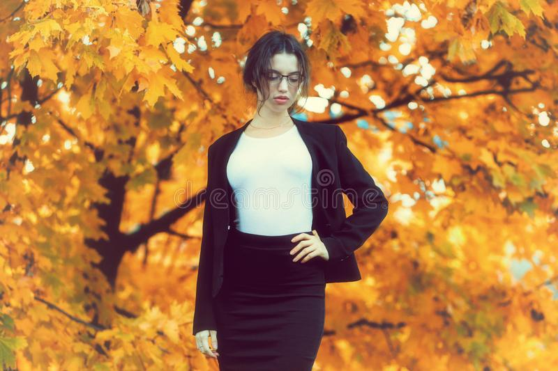 Business woman in formal wear stands over yellow autumn trees. Young business woman in formal wear stands over yellow autumn trees royalty free stock photography
