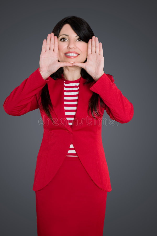 Business woman framing face. Attractive smiling business woman in smart red skirt suit frames her face with her hands royalty free stock image