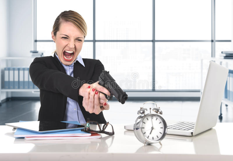 Business woman furious and angry working with computer laptop pointing gun to alarm clock royalty free stock image