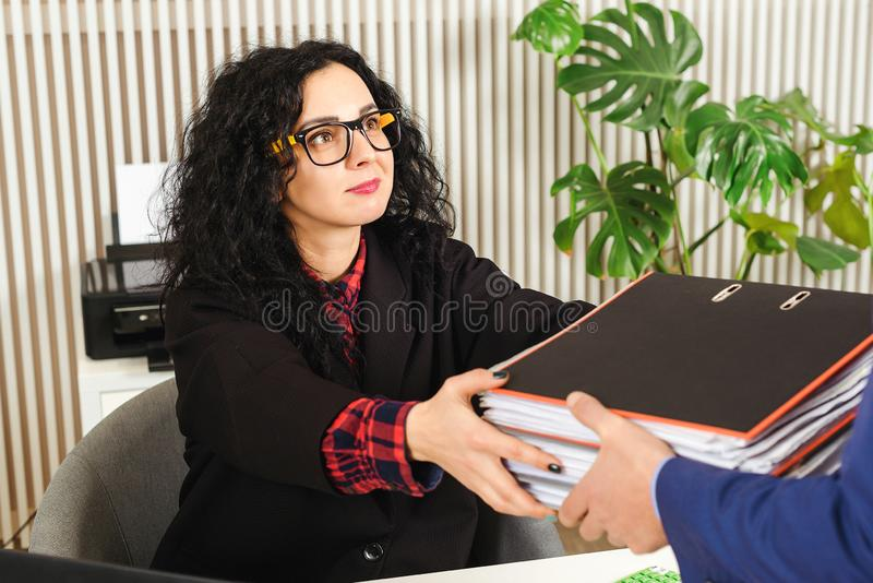 Business woman gets a stack with documents. Business documents concept. Accountant at workplace in office. Woman searching royalty free stock photos