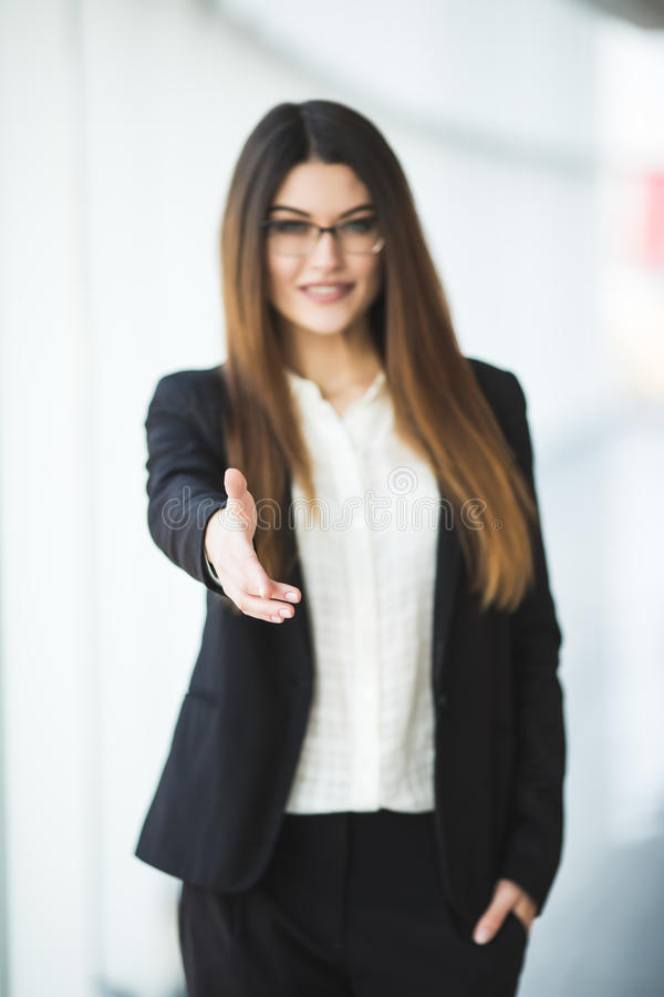 Business woman giving a hand. handshake in the office stock photography