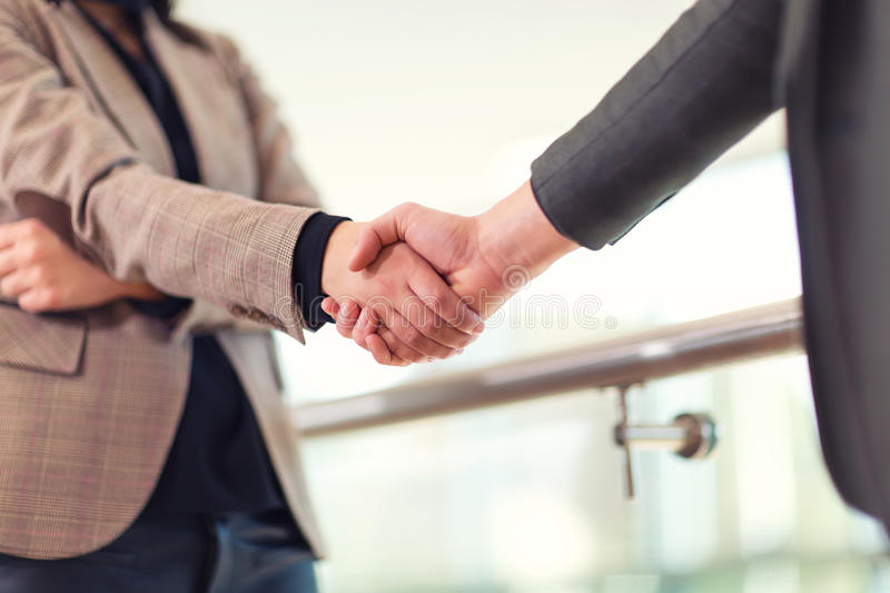 Business woman giving a handshake. To business man royalty free stock photo