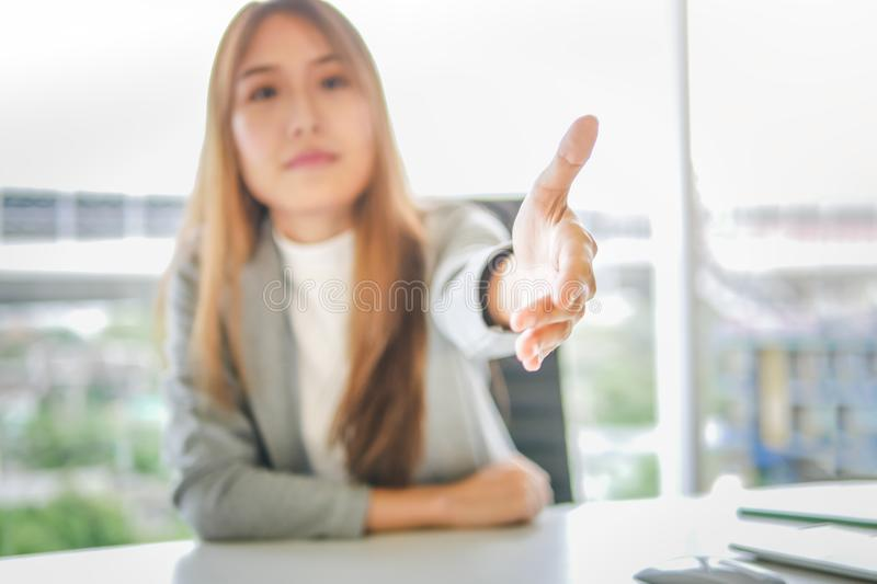 Business woman giving her hand for handshake to partner ,partnership deal successful concept.  stock photography
