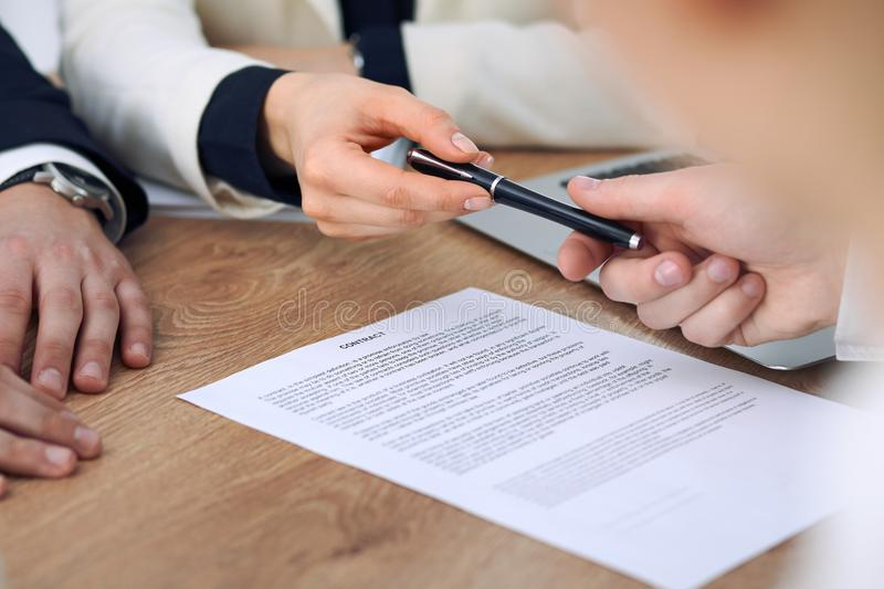 Business woman giving pen to businessman ready to sign contract. Success communication at meeting or negotiation stock images
