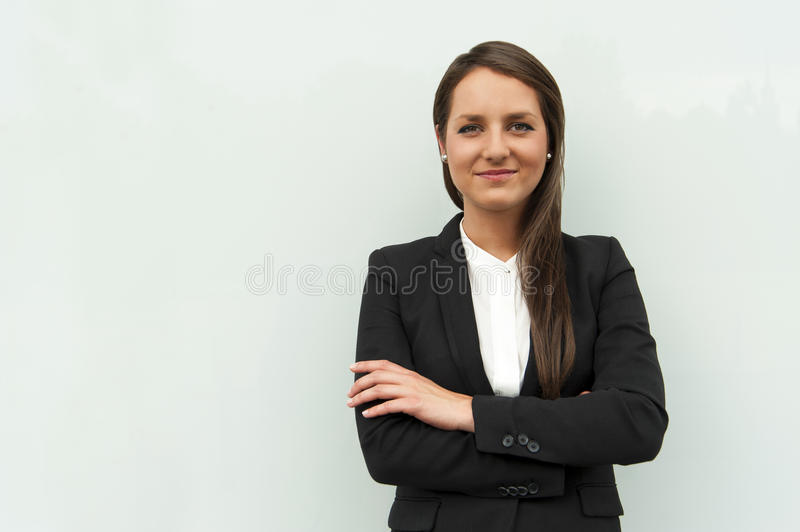 Business woman by the glass wall in the city smiling at camera. Business woman by the glass wall in the city smiling at camera in business siute royalty free stock photography