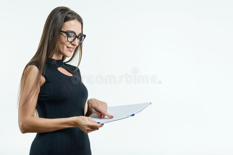 Business woman in glasses black dress reading document. White background, copy space stock photos