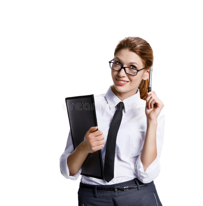 Business woman in glasses with a folder and pen stands. Stock image of woman holding a pen and clipboard - isolated on white background royalty free stock photography