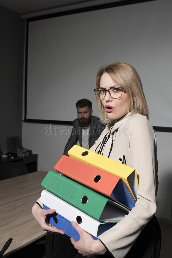 Business woman in glasses hold file folders. secretary with office documents. Surprised woman and bearded man on royalty free stock photo