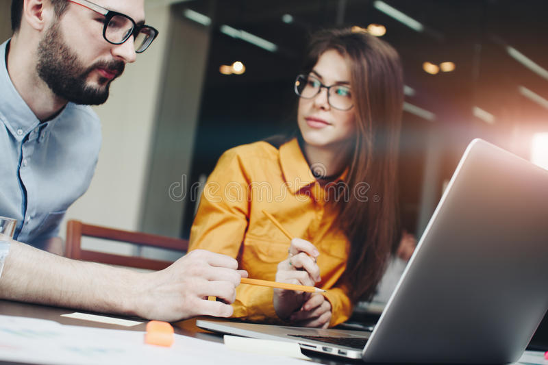 Business woman in glasses shows a colleague a project on a laptop. Discussing marketing plan. Laptop and paperwork on the table stock photo