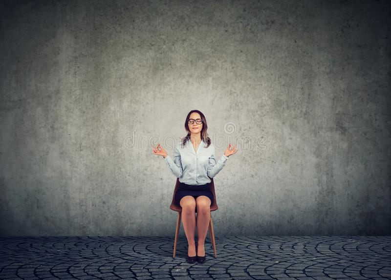 Meditating woman on chair with eyes closed royalty free stock photography