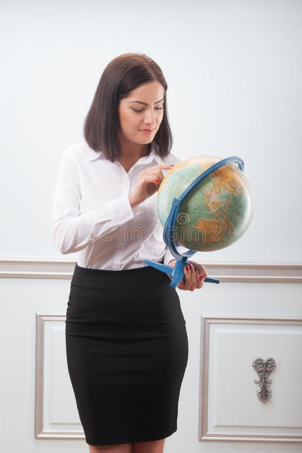 Business woman with the globe. Beautiful business woman with nice haircut wearing white blouse and black skirt looking at the globe very attentively decided stock image