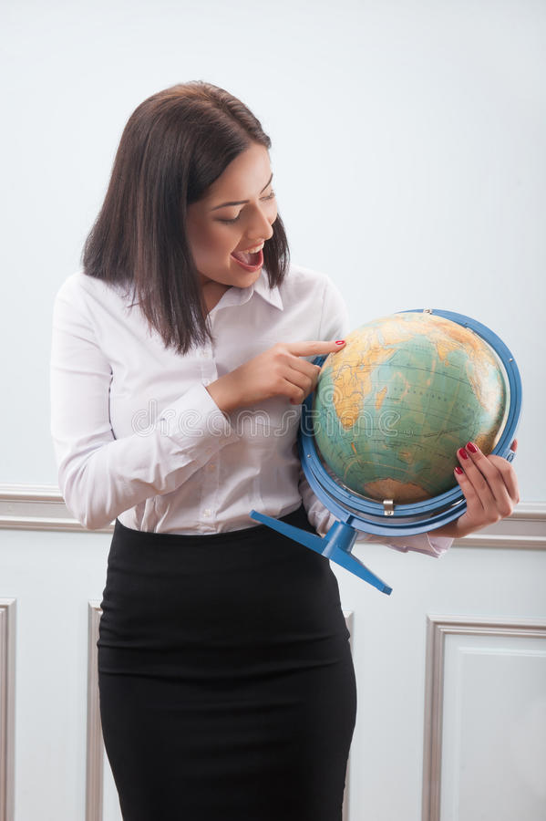 Business woman with the globe. Beautiful business woman with nice haircut wearing white blouse and black skirt looking at the globe very attentively decided royalty free stock photos