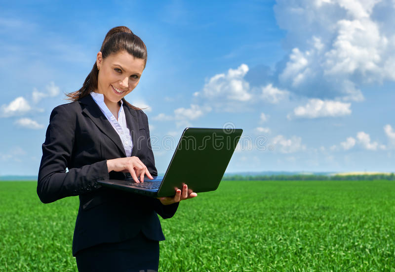 Business woman in green grass field outdoor work on laptop. Young girl dressed in black suit. Beautiful spring landscape with clou. Dy sky, bright sunny day royalty free stock photography