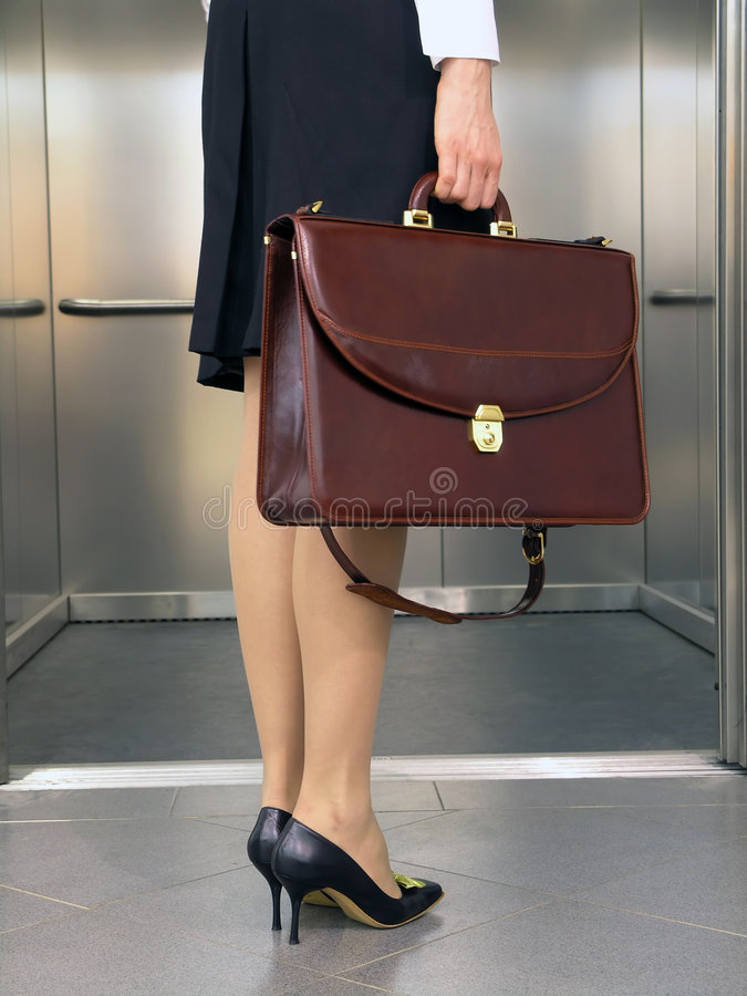 Business woman with hand-bag. Entry into elevator royalty free stock images