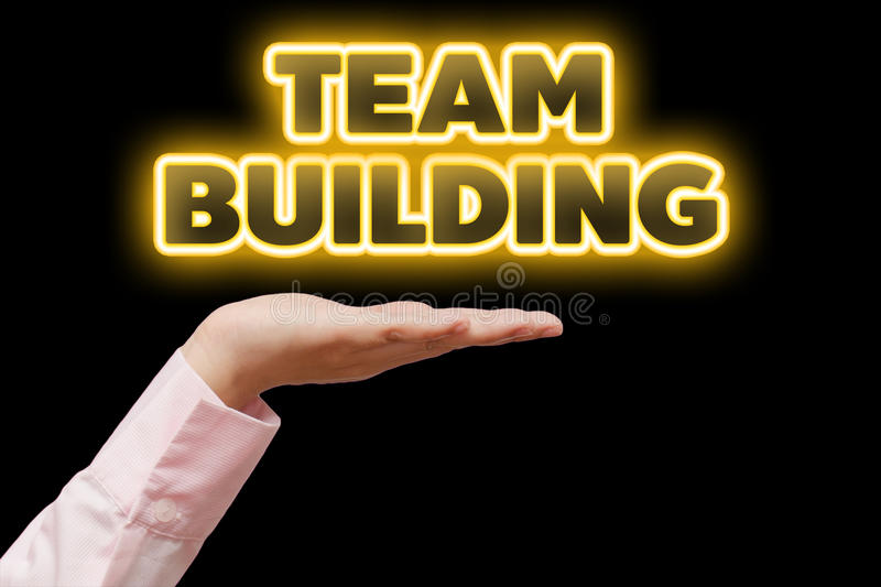 Business woman hand cupped holding the word TEAM BUILDING with orange yellow light royalty free stock image