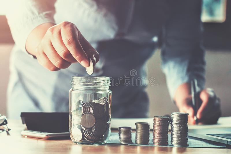 business woman hand holding coins puting into glass. concept saving money finance and accounting royalty free stock image
