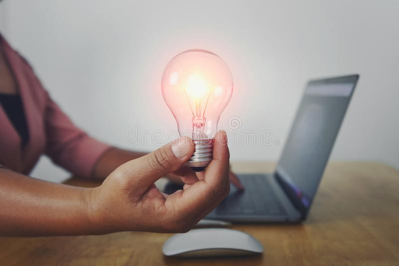 Business woman hand holding light bulb with using laptop in office. concept saving energy power. Accounting, money, electricity, finance, lightbulb, save royalty free stock photo