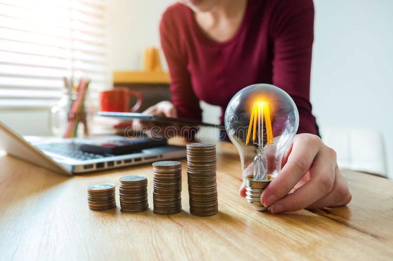Business woman hand holding lightbulb with coins stack on desk. concept saving energy. stock photos