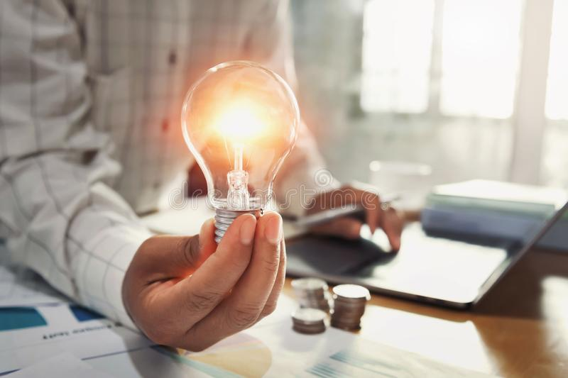 Business woman hand holding lightbulb with coins stack on desk. concept saving energy power. Accounting, money, electricity, finance, save, knowledge royalty free stock photography