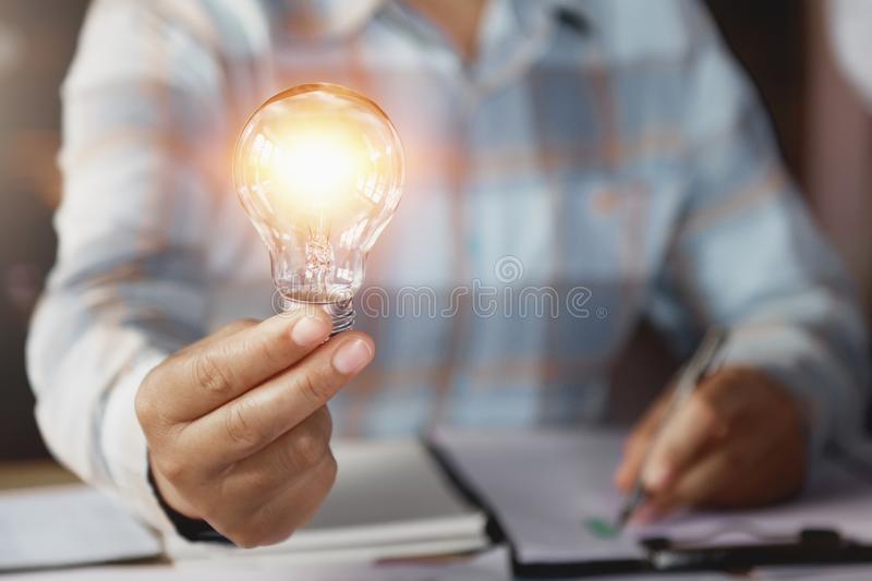 Business woman hand holding lightbulb in office. concept saving energy. Power royalty free stock image