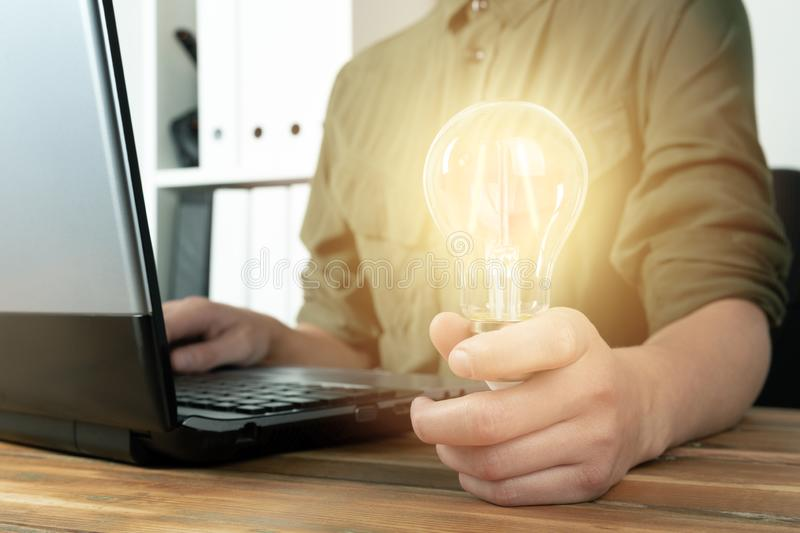 Business woman hand holding lightbulb in office. Concept saving energy, idean and creativity royalty free stock images