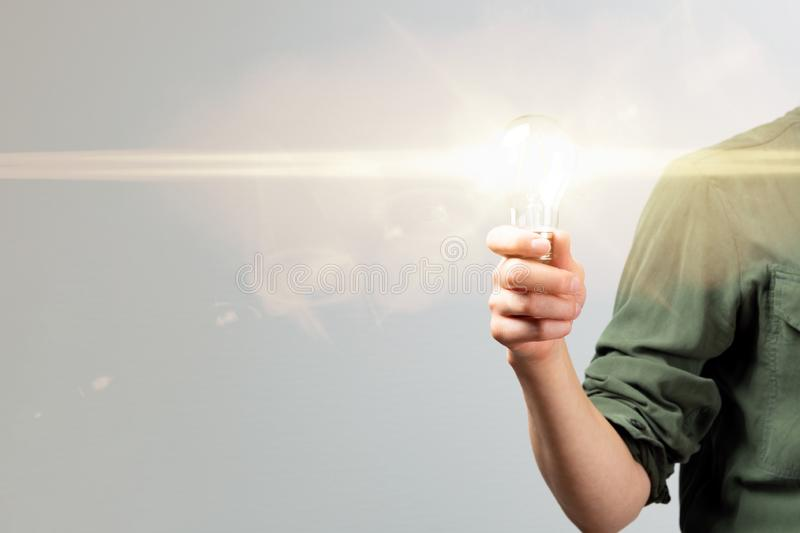 Business woman hand holding lightbulb in office. Concept saving energy, idean and creativity royalty free stock photo