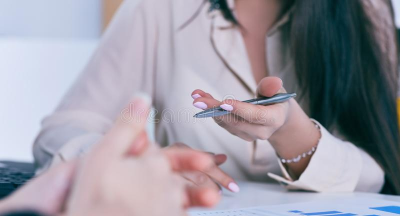 Business woman hand holding pen and pointing at financial diagram, graph during conference sitting at the office desk. royalty free stock photos