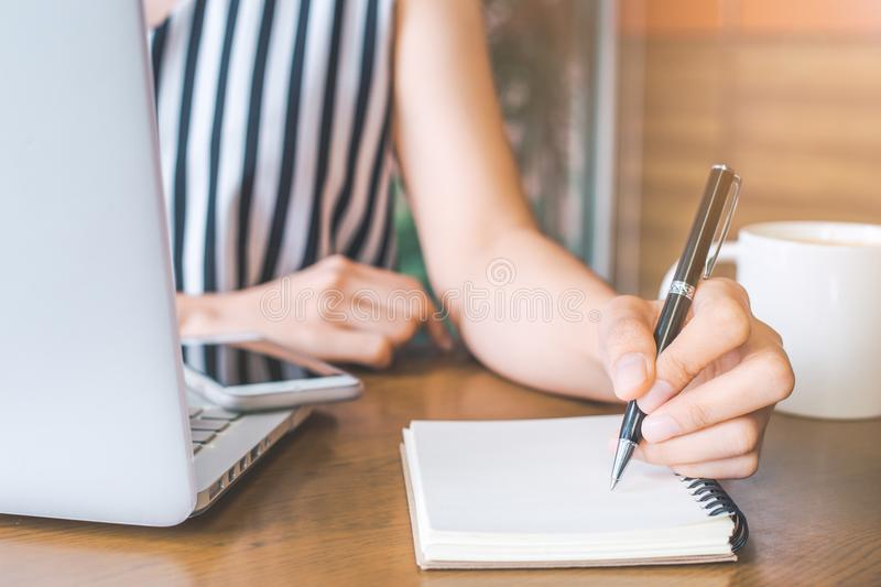 Business woman hand working at a computer and writing on a noteped with a pen in the office. stock photos