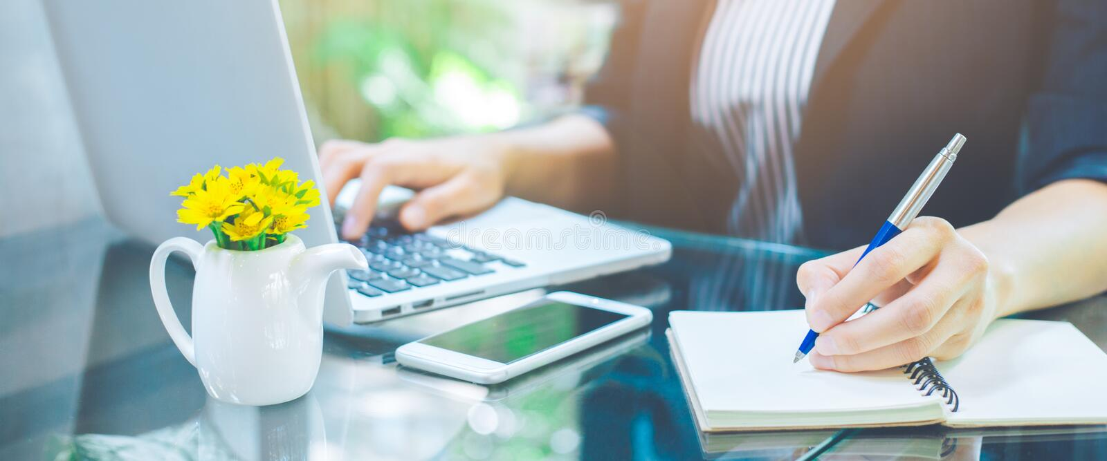 Business woman hand is writing notebook with a pen and using a laptop computer in the office stock photos