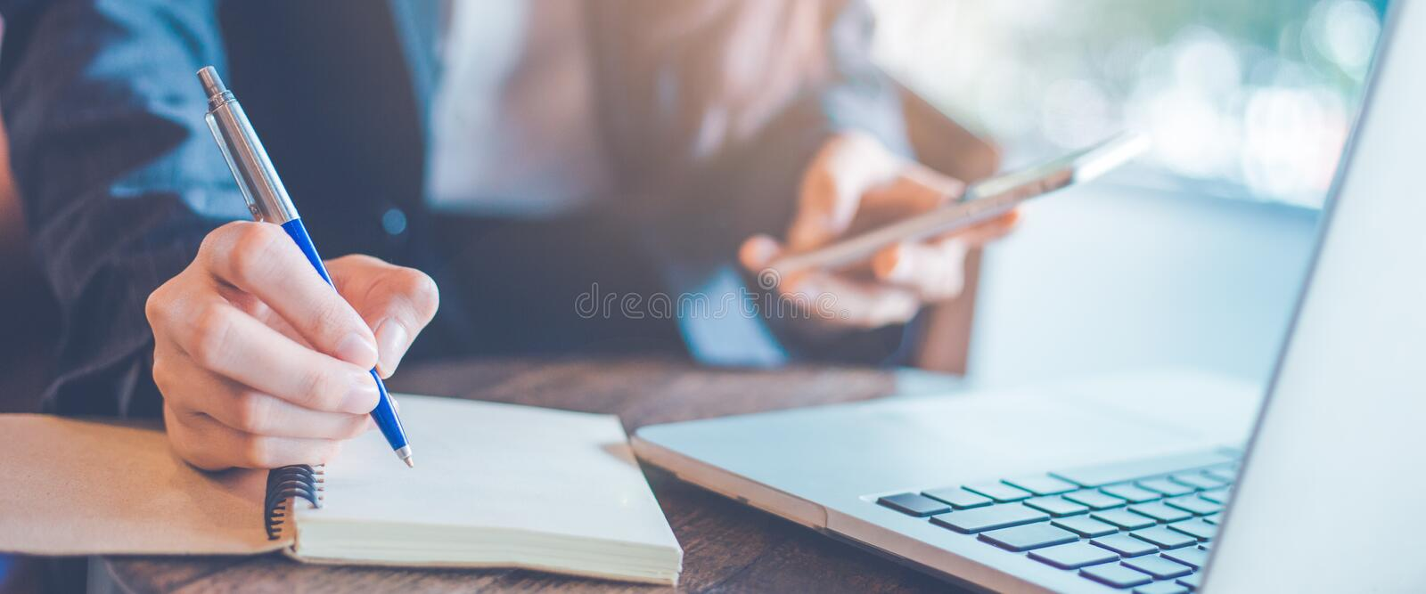 Business woman hand writing on a notepad with a pen in the offi stock images