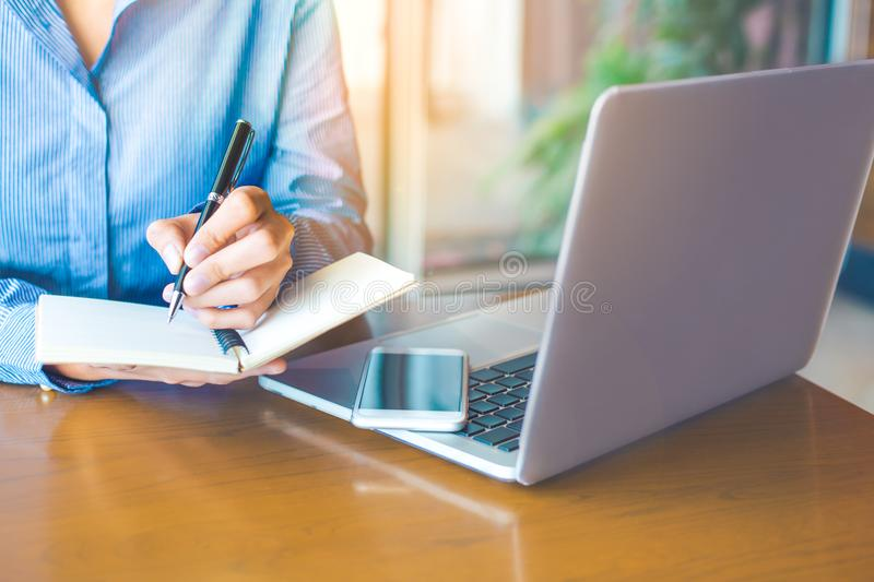 Business woman hand is writing on notepad with pen in office.On the wood table there are cell phones and laptops. Business woman hand is writing on notepad with stock photos