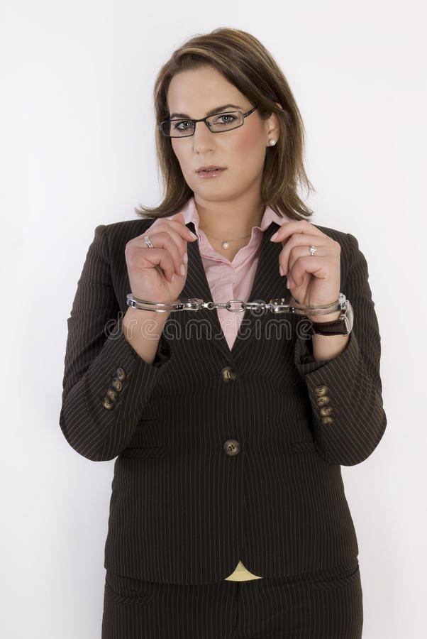 Business woman with handcuffs on her hands. royalty free stock image