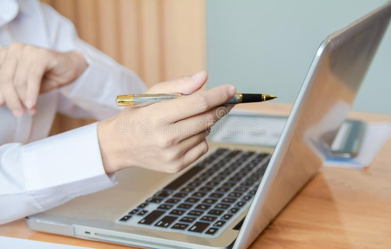 Business woman hands holding pen and using laptop with blank screen on desk in cafe royalty free stock photography