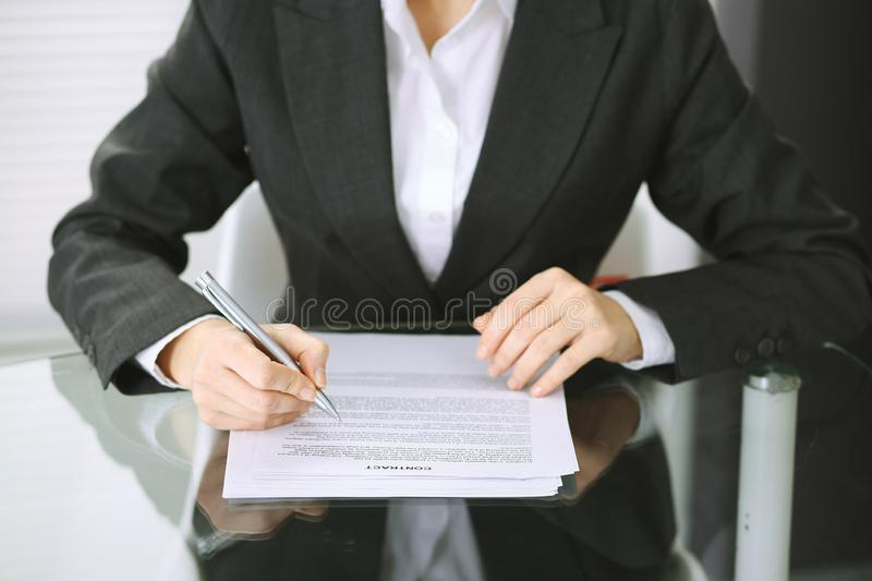 Business woman hands with pen over document of contract at glass table. Agreement signing concept.  stock images
