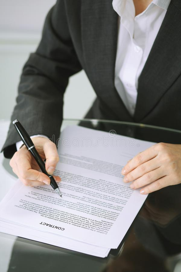 Business woman hands with pen over document of contract at glass table. Agreement signing concept.  royalty free stock photography