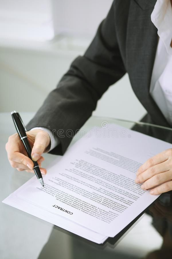 Business woman hands with pen over document of contract at glass table. Agreement signing concept.  royalty free stock images