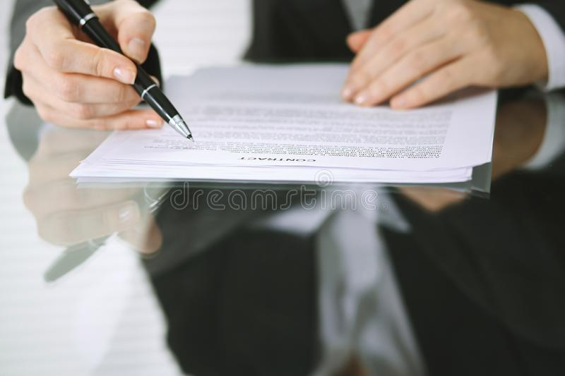 Business woman hands with pen over document of contract at glass table. Agreement signing concept.  stock photo