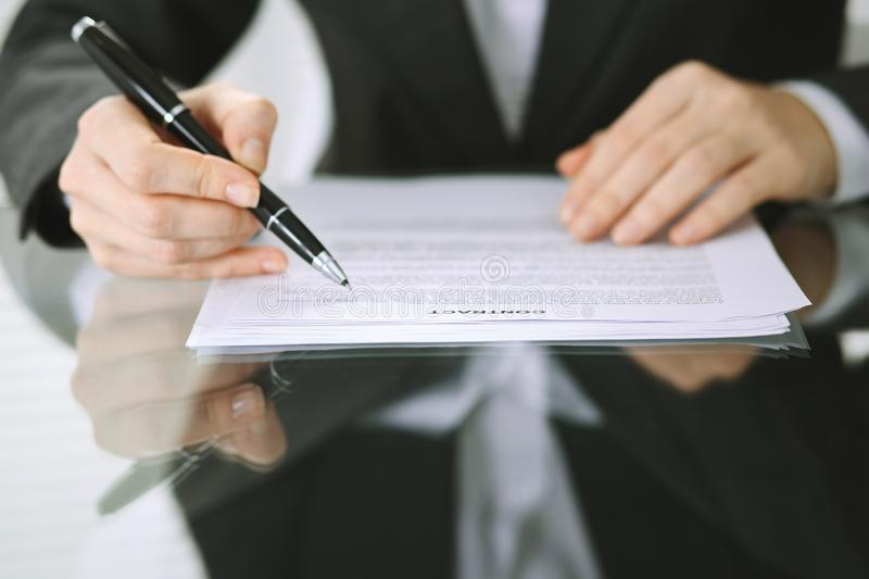 Business woman hands with pen over document of contract at glass table. Agreement signing concept.  royalty free stock photos