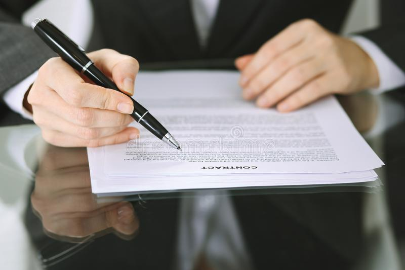Business woman hands with pen over document of contract at glass table. Agreement signing concept.  stock image