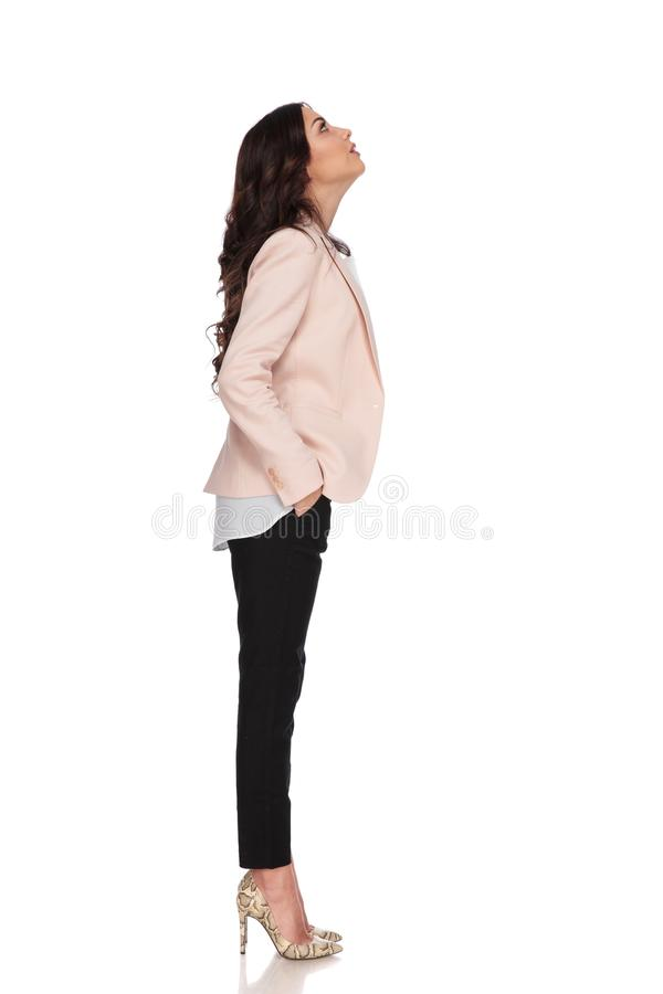Business woman with hands in pockets looks up royalty free stock photo