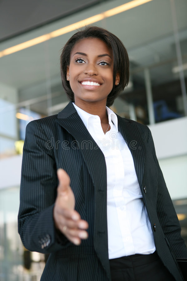 Business Woman Handshake. A pretty african american business woman offering a handshake stock photography