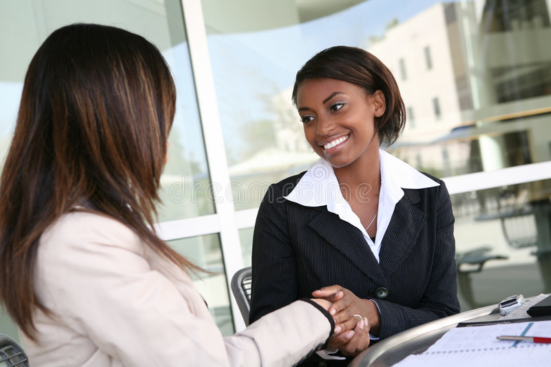 Business Woman Handshake. A pretty african american business woman shaking hands royalty free stock photo