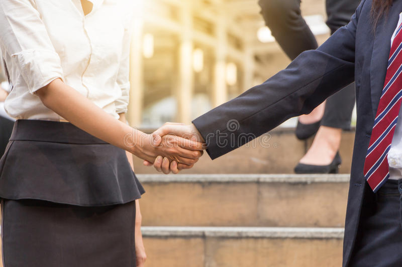 Business woman handshake at city background. stock image