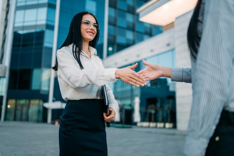 Business woman, handshake with partner outdoor. Business woman in glasses and white blouse, handshake with partner outdoor. Modern building, financial center stock images